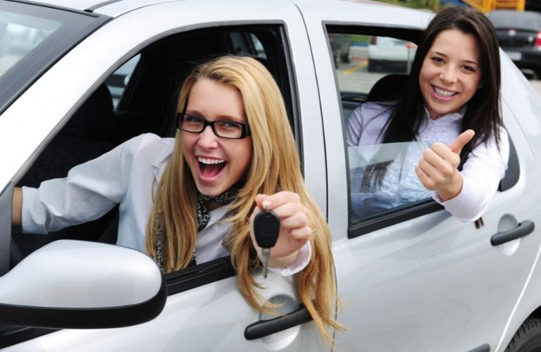 two happy woman with key hand sitting inside a car