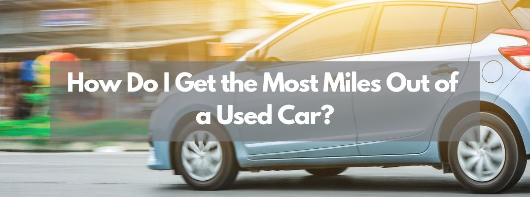 "Blue car driving with ""How Do I Get the Most Miles Out of a Used Car?"" white text"