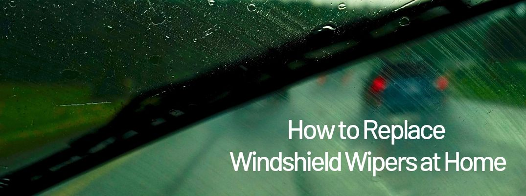 "View out of dirty car windshield with ""How to Replace Windshield Wipers at Home"" white text"