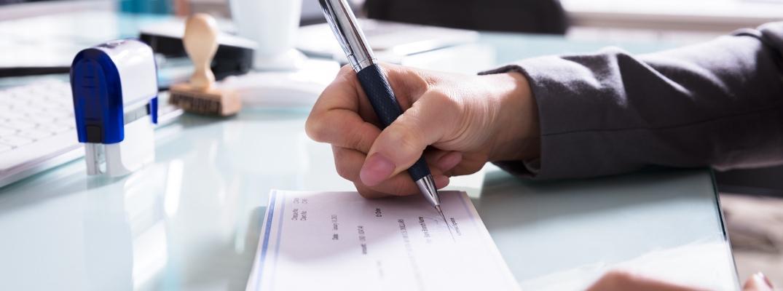Closeup of hand signing check