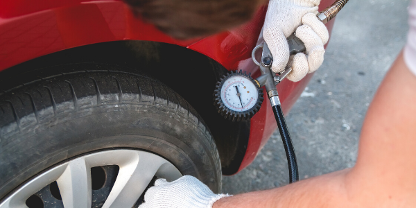 Hand checking tire's air pressure with gauge