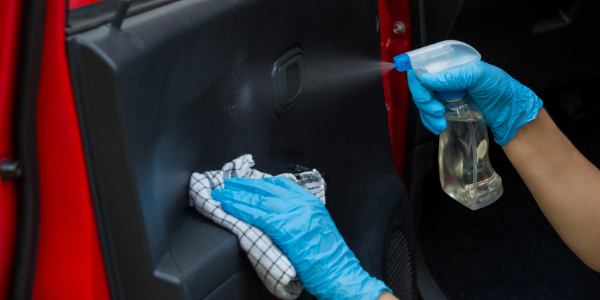 Closeup of hands with blue gloves on disinfecting the interior of a vehicle with spray