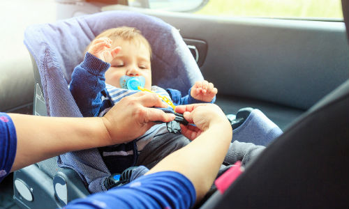 Baby being buckled in car seat