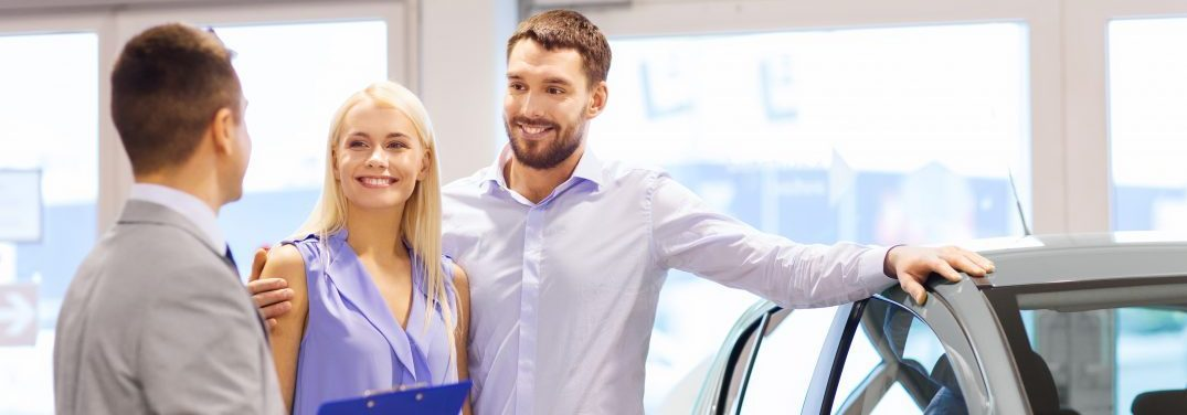 sales man speaking with young couple interested in a new vehicle