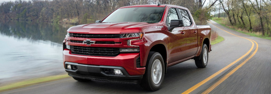 red 2019 Chevy Silverado driving along a lake