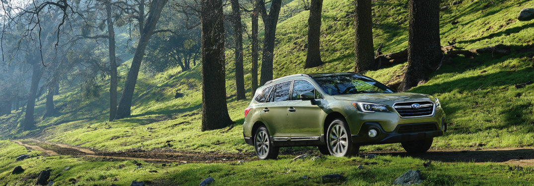subaru outback driving along a hill on a road