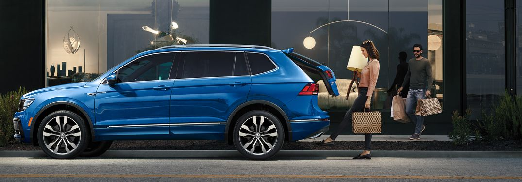 A woman putting luggage inside of a 2020 Volkswagen Tiguan