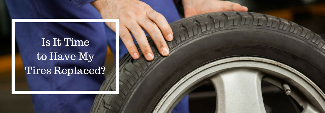Is It Time to Have My Tires Replaced, text on an image of a mechanic rolling a new tire