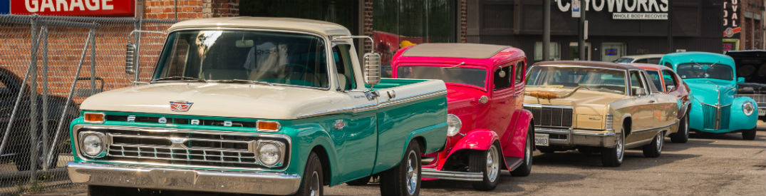 Classic cars and trucks lined up on the street