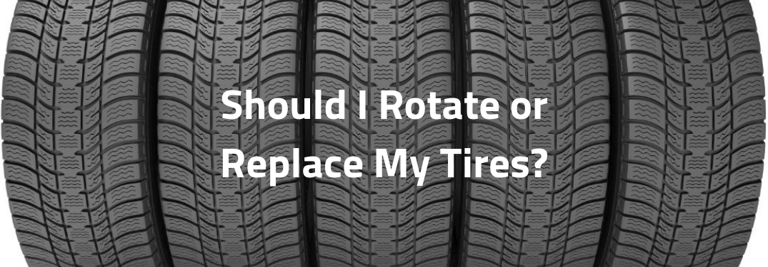 Should I Rotate or Replace My Tires, text on an image of five new tires lined up next to each other