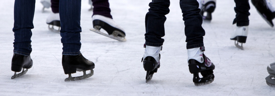 Close-up on people's feet skating on the ice
