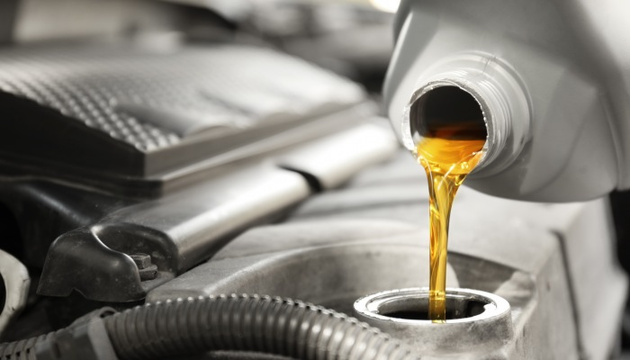 Close-up of a person pouring oil into an engine