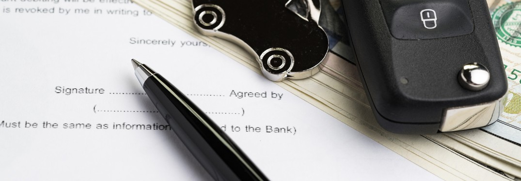 Pen resting on financing agreement next to vehicle keys