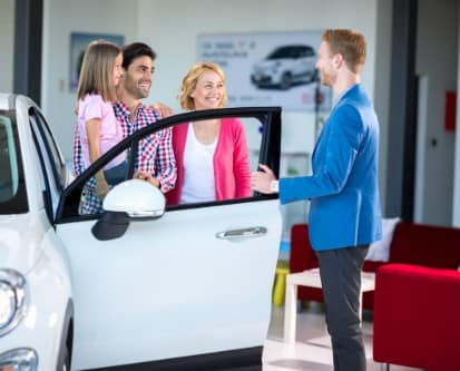 A husband, wife and daughter standing next to the open door of a car talking to a salesman at a dealership