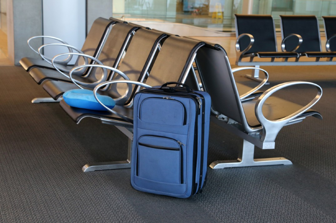 A blue suitcase next to chairs at an airport
