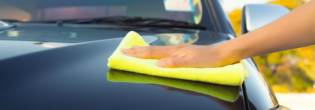 person using microfiber towel to dry off car