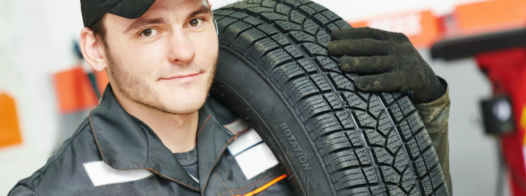 Service technician carrying a tire