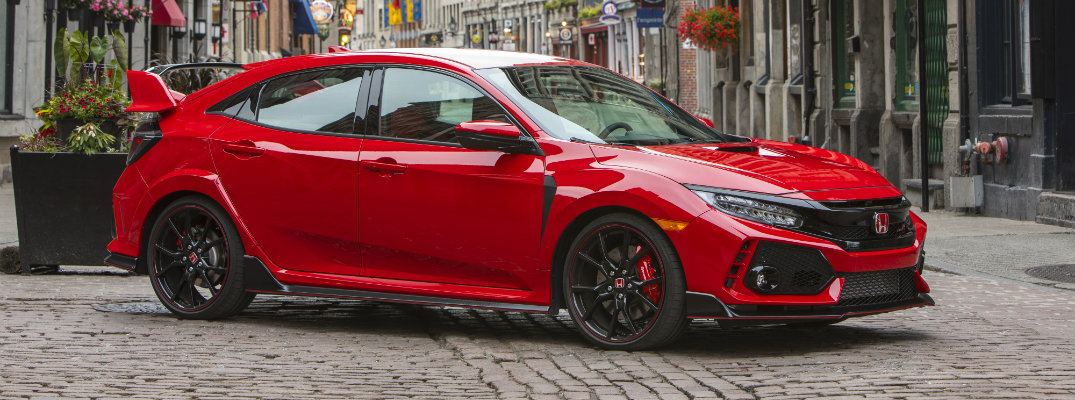 2019 Honda Civic Type R exterior side shot with red paint color parked on a tile road between stone buildings in a foreign country