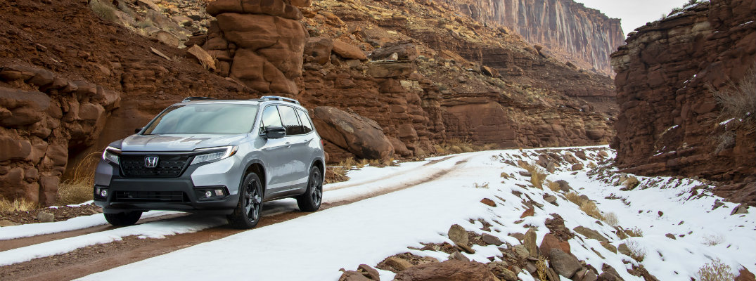 2019 Honda Passport exterior shot with silver metallic paint color driving through a snowy mountain canyon path