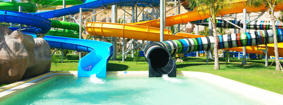 a bunch of water slide tubes emptying into a pool at a water park tropical resort