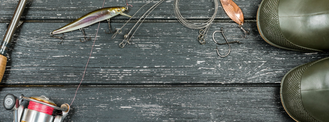 a fishing rod, bait, tackle, net, and a pair of green seat boots on top of a black wood lake pier