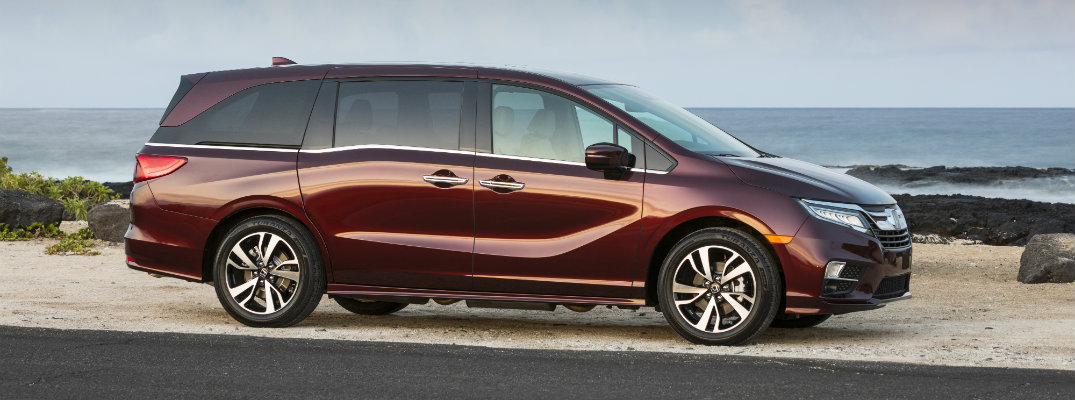 2019 Honda Odyssey red maroon exterior shot parked off the road on a beach next to waves, rocks, and a cloudy sky