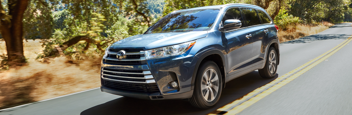 Blue 2018 Toyota Highlander driving down the highway during the day