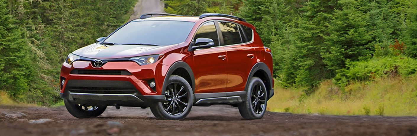 Red 2018 Toyota Rav4 parked in the woods