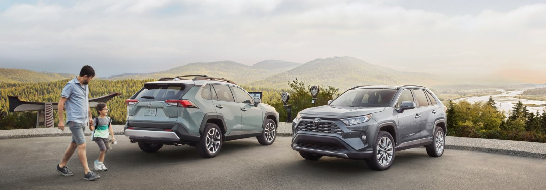 A man and his son walk towards a parked 2019 Toyota RAV4