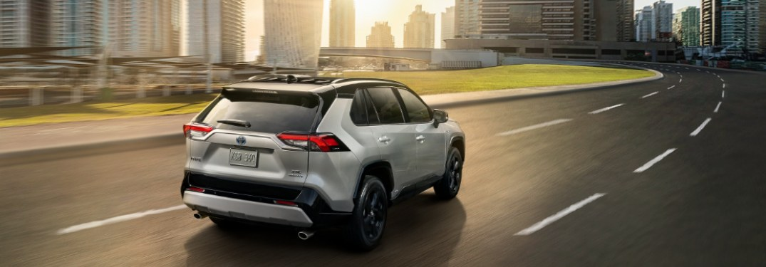 2019 Toyota RAV4 driving down a highway road leading in to a city