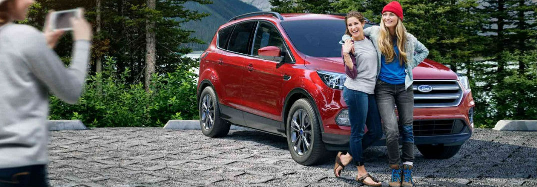 2018 Ford Escape parked with with two women in front posing for a picture