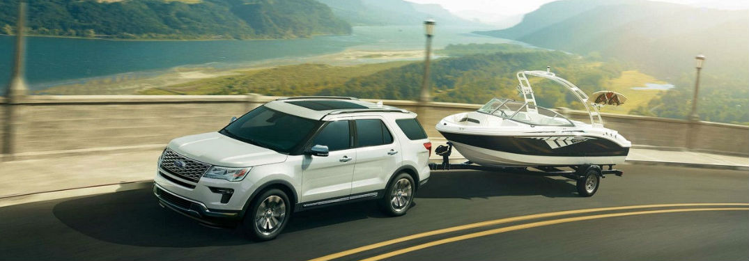 Ford Explorer driving on a road and pulling a trailer with a boat on it