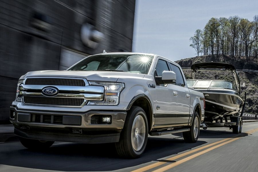 2020 Ford F-150 King Ranch towing a boat down road from exterior front drivers side