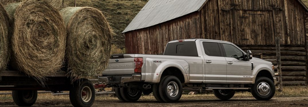2020 Ford Super Duty truck towing hay in front of barn from exterior passenger rear
