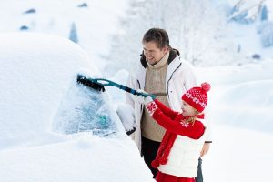 Dad and daughter scraping snow from car_c