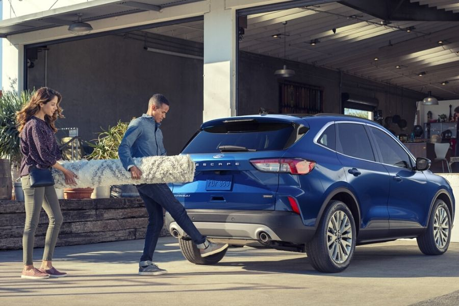 Man holding rug and activating the hands-free lift-gate on the 2020 Ford Escape