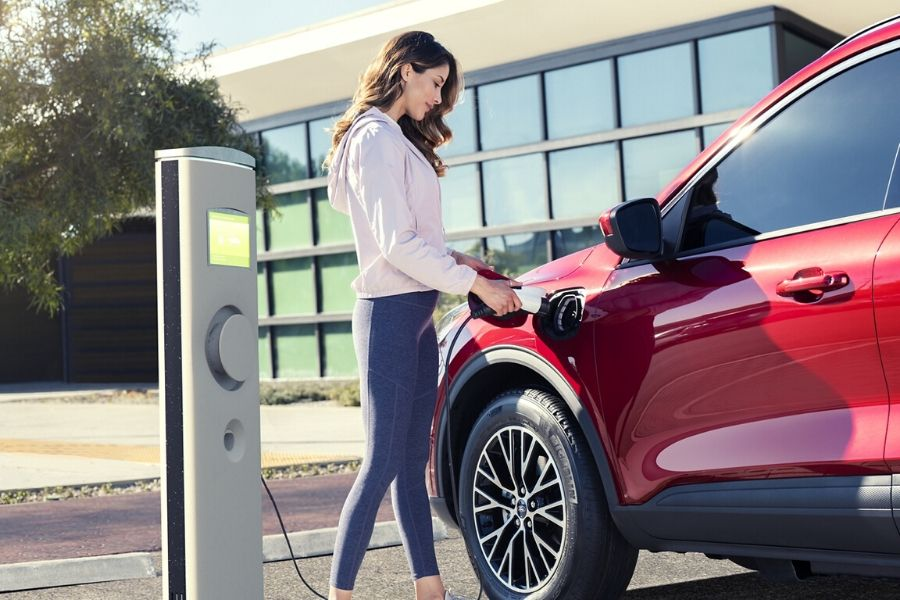 Woman plugging in 2020 Ford Escape hybrid charger