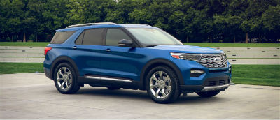 Atlas Blue 2020 Ford Explorer exterior front fascia passenger side in front of trees