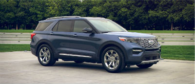 Blue Metallic 2020 Ford Explorer exterior front fascia passenger side in front of trees