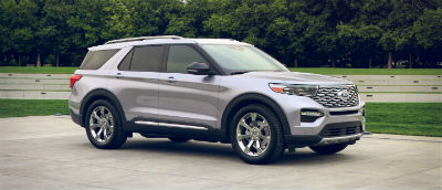 Iconic Silver 2020 Ford Explorer exterior front fascia passenger side in front of trees