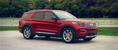 Rapid Red Metallic 2020 Ford Explorer exterior front fascia passenger side in front of trees