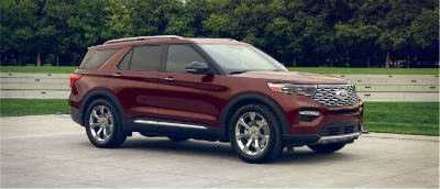 Rich Copper Metallic 2020 Ford Explorer exterior front fascia passenger side in front of trees