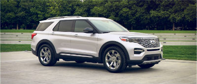 Star White Metallic 2020 Ford Explorer exterior front fascia passenger side in front of trees