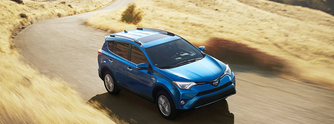Long shot of blue 2018 Toyota RAV4 Hybrid model driving down grassy road