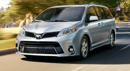 Silver 2018 Toyota Sienna driving down parkway in broad daylight