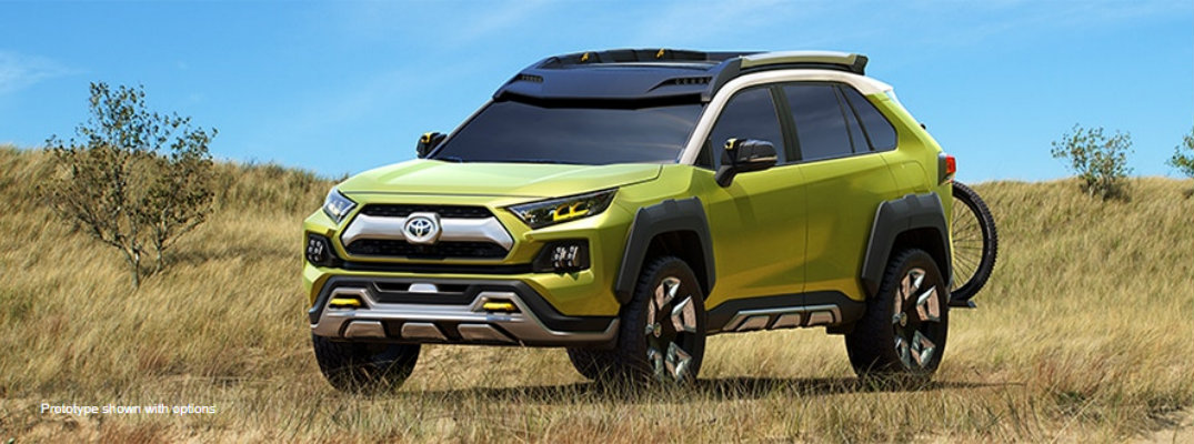 Long shot of green Toyota FT-AC concept model parked in field with daylight surrounding