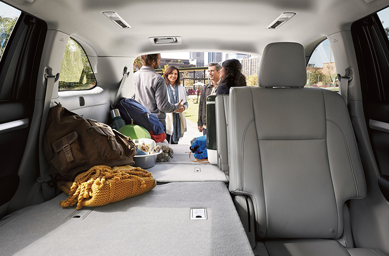 Group of people storing cargo in back of 2018 Toyota Highlander