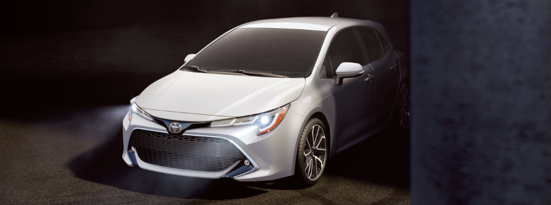 White 2019 Toyota Corolla Hatchback parked next to pillar with headlights illuminating