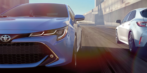 Blue and white 2019 Toyota Corolla Hatchback models driving opposite one another on road