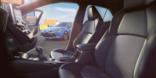 Front two seats of 2019 Toyota Corolla Hatchback with center console in frame